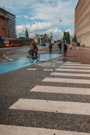 Photo pour COPENHAGUE, DANEMARK - 30 AVRIL 2020 : Les gens marchent et font du vélo dans la rue urbaine avec un ciel nuageux en arrière-plan - image libre de droit