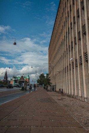 Photo pour Rue urbaine avec passerelle près du bâtiment et route avec ciel nuageux en arrière-plan à Copenhague, Danemark - image libre de droit