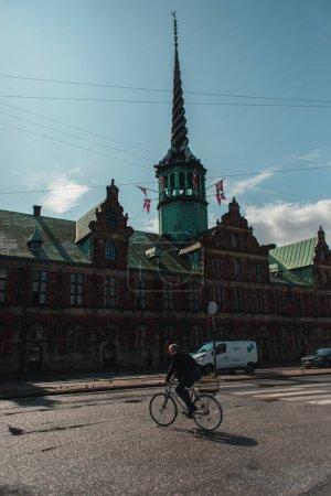 Photo pour COPENHAGUE, DANEMARK - 30 AVRIL 2020 : Homme roulant sur la route près de la façade de Borsen dans la rue urbaine - image libre de droit