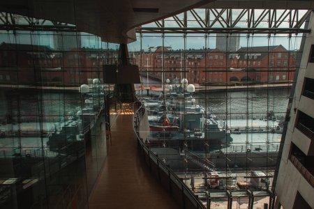 COPENHAGEN, DENMARK - APRIL 30, 2020: Interior of danish royal library with docked ships in harbor near facade, Copenhagen, Denmark