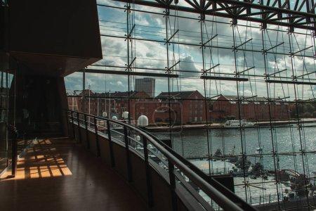 COPENHAGEN, DENMARK - APRIL 30, 2020: Glass facade of Black Diamond Royal Library with ship in harbor at background, Copenhagen, Denmark