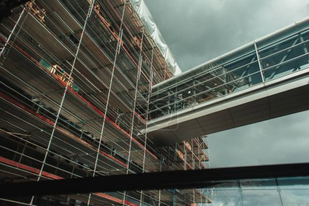 Photo for Low angle view of building construction with glass corridor and cloudy sky at background in Copenhagen, Denmark - Royalty Free Image