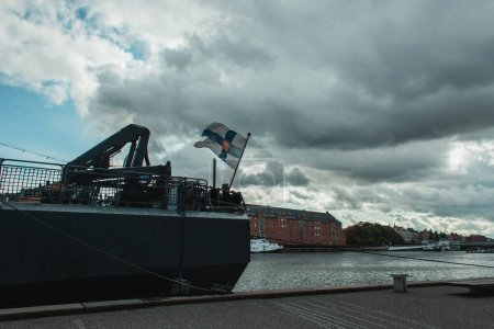 Docked ship on canal with buildings and cloudy sky at background, Copenhagen, Denmark