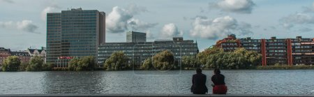 Photo pour Récolte panoramique de personnes assises sur la promenade près du canal avec des bâtiments et un ciel nuageux en arrière-plan, Copenhague, Danemark - image libre de droit