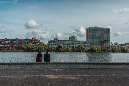 Photo pour Personnes assises sur la promenade près du canal avec des bâtiments et un ciel nuageux en arrière-plan, Copenhague, Danemark - image libre de droit
