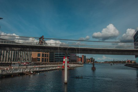 Photo for COPENHAGEN, DENMARK - APRIL 30, 2020: People cycling on bridge above river with urban street and sky with clouds at background - Royalty Free Image