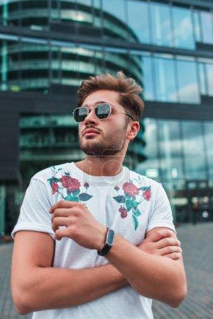 Photo pour Jeune homme en lunettes de soleil regardant loin sur la rue urbaine - image libre de droit