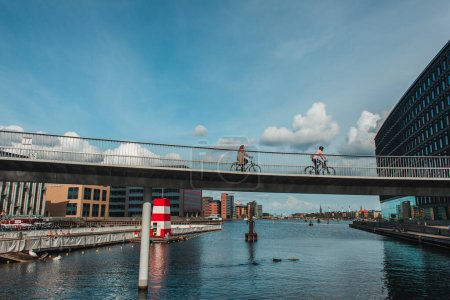 Photo for COPENHAGEN, DENMARK - APRIL 30, 2020: People riding bicycles on bridge above river with buildings and cloudy sky at background - Royalty Free Image