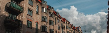 Photo for Panoramic orientation of facade of old building with sunlight and cloudy sky at background, Copenhagen, Denmark - Royalty Free Image