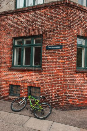 Bicycle on walkway near brick facade of building in Copenhagen, Denmark