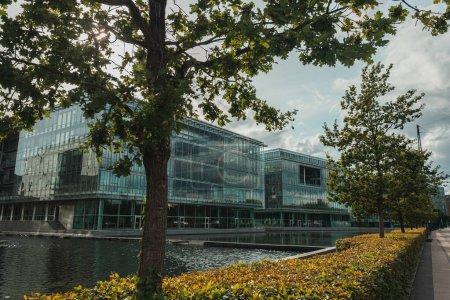 Photo pour Arbres près du canal et bâtiment avec façade vitrée sur rue urbaine, Copenhague, Danemark - image libre de droit