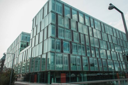 Low angle view of glass facade of building near lanterns on urban street, Copenhagen, Denmark