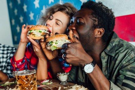 Frau ruht mit Mann in Bar, redet, lacht, isst Fast Food