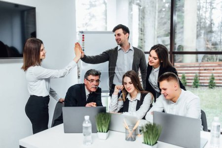 Photo for Creative workers in modern office sitting with laptops and discussing something - Royalty Free Image