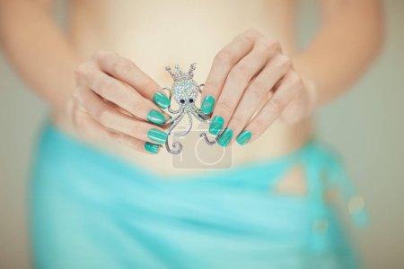 Photo pour Belles mains de femme avec vernis à ongles bleu parfait tenant petite broche poulpe, humeur plage bikini heureux, peut être utilisé comme fond - image libre de droit