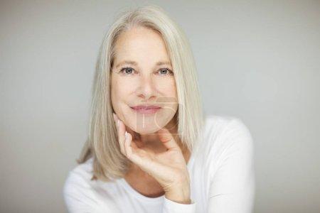Foto de Impresionante hermosa y auto confianza mejor de años a mujer con canas, sonriendo a la cámara, retratos con fondo blanco - Imagen libre de derechos