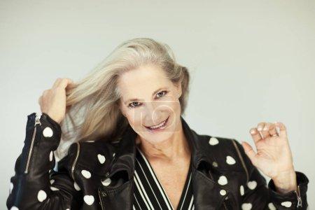 Photo pour Superbe belle et libre confiant meilleur âgés de femme avec des cheveux gris parfaite, coiffure, souriant à la caméra, portrait avec fond blanc - image libre de droit