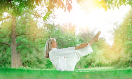 Photo pour Beau meilleur âge Femme âgée aux longs cheveux gris faisant des exercices de yoga à l'extérieur - image libre de droit