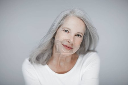 stunning beautiful and self confident best aged woman with grey hair smiling into camera