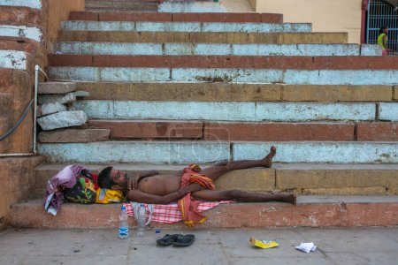 VARANASI, INDIA - MAR 23, 2018: Beggar tramp sleeping on the street of the old town near the Holy Ganges river.