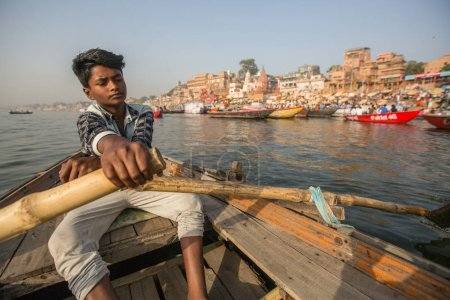 VARANASI, INDIA - MAR 26, 2018: Boatmen on a boat glides through water on Ganges river along shore of Varanasi. According to legends, Varanasi was founded by God Shiva about 5000 years ago.