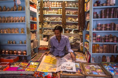 VARANASI, INDIA - MAR 23, 2018: Seller on the banks of the sacred Ganges river selling souvenirs in his street shop.