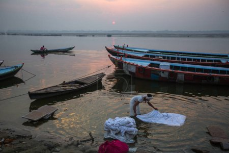 VARANASI, INDIA - MAR 22, 2018: A man washes sheets in the Holy Ganga river. Varanasi is one of the most important pilgrimage sites in India and is one of the 7 sacred cities of Hinduism.