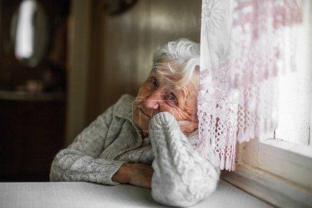 Sad old woman sitting near the window.
