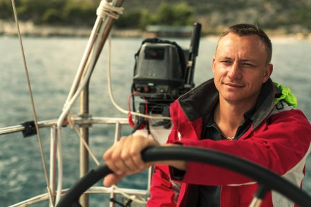 Photo for Skipper at the helm the sail yachts boat control during sea race. - Royalty Free Image