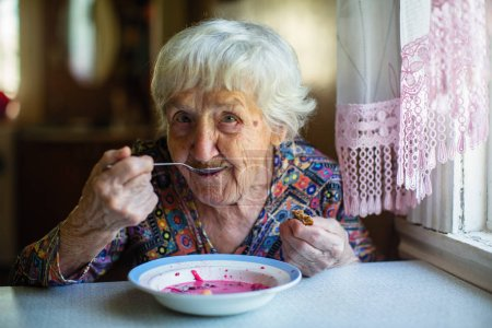 Photo for An elderly woman eating soup borsch sitting at the table. - Royalty Free Image