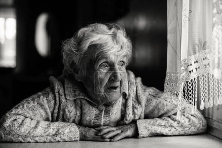 Black and white portrait of an elderly woman sitting near the window.
