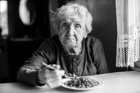 An elderly woman eats sitting at the table. Black and white photo.