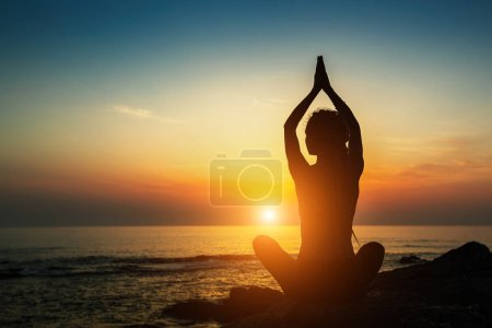 Yoga woman silhouette. Meditation on the ocean during amazing sunset.