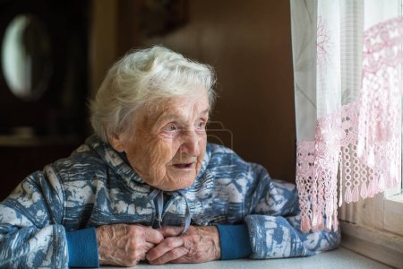 Photo for Elderly pensioner woman looks out the window. Old lady, granny. - Royalty Free Image