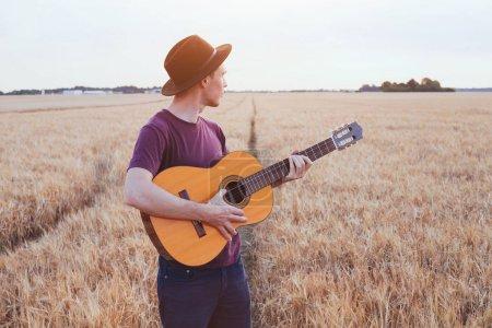 Photo pour Jeune homme jouant de la guitare sur le terrain au coucher du soleil, chanson d'amour romantique - image libre de droit