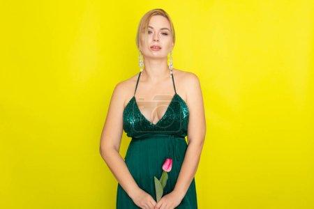 Photo pour Femme blonde en robe de soirée verte tenant une tulipe dans ses mains sur fond jaune - image libre de droit