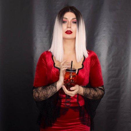 Photo pour Jeune belle femme blonde dans une robe vampire rouge tient un verre orange en forme de crâne dans ses mains - image libre de droit