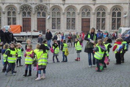 Photo pour Groupe d'enfants en gilets réfléchissants avec des adultes marchant près du vieil immeuble en ville - image libre de droit