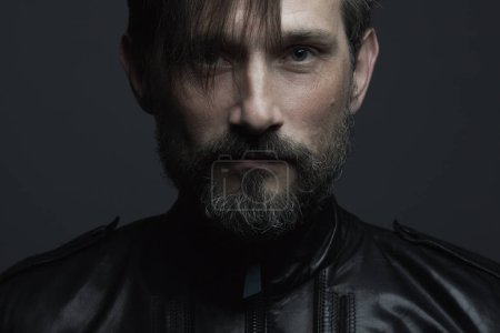 Photo for Fabulous at any age. Portrait of 40-year-old man in black leather jacket standing over dark gray background. Long hair on forehead. Rocker, biker style. Close up. Studio shot - Royalty Free Image
