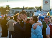 Munich, Germany - October 07, 2018: Two young guys kiss on the lips at the biggest folk festival in the world - the Oktoberfest.