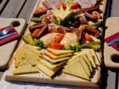 Cheese, meat and vegetable slices on a wooden board.