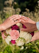 Hands of the bride and groom on the wedding bouquet.