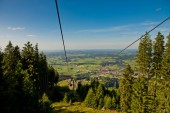 Mountain landscape with forest and ski lift on a sunny day.
