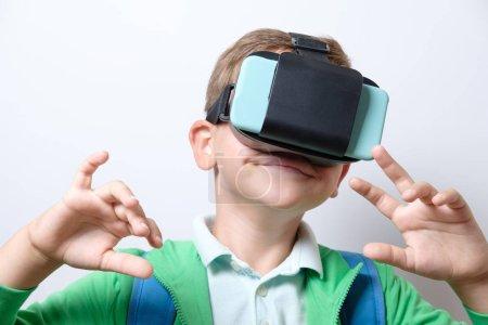 Photo pour Écolier mignon avec sac à dos bleu Port casque de réalité virtuelle avec les bras tendu vers l'avant sur un fond blanc - image libre de droit