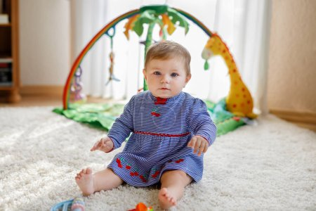 Photo for Adorable baby girl playing with educational toys in nursery. Happy cute healthy child having fun with colorful different toys. Toddler learning different skills like throwing catching ball - Royalty Free Image