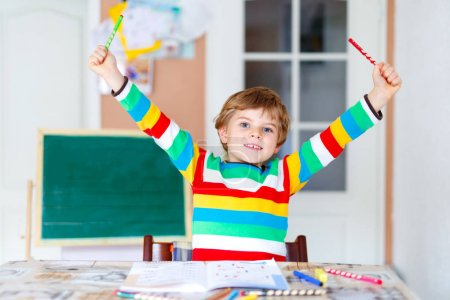Photo for Portrait of cute happy school kid boy at home making homework. Little child writing with colorful pencils, indoors. Elementary school and education. - Royalty Free Image