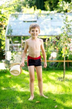Photo pour Garçon enfant actif mignon sauter dans le jardin ensoleillé chaude journée d'été. Enfant heureux en regardant la caméra. Enfant adorable avec des cheveux blonds et les yeux bleus. - image libre de droit