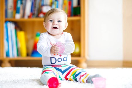 Photo for Adorable baby girl playing with educational toys in nursery. Happy healthy child having fun with colorful different toys at home. Baby development and first steps, learning to play and to grab - Royalty Free Image