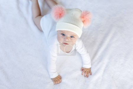 Photo for Cute adorable baby child with warm white and pink hat with cute bobbles. Happy baby girl learning crawl and looking at the camera. Close-up for xmas holiday and family concept. - Royalty Free Image