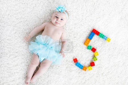 Photo for Adorable baby girl on white background wearing turquoise tutu skirt. Cute little child laughing and smiling. Happy carefree baby. Childhood, new life concept. - Royalty Free Image